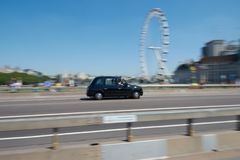 LONDON - June 26, 2018 : Black cab is driving along th. LONDON / ENGLAND - June 26, 2018 : Black cab is driving along the Westminster Bridge and Coca-Cola London royalty free stock images