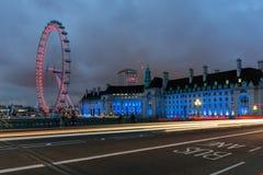 LONDON ENGLAND - JUNI 16 2016: Nattfoto av det London ögat och den ståndsmässiga Hallen från den Westminster bron, London, stor b Fotografering för Bildbyråer