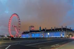 LONDON ENGLAND - JUNI 16 2016: Nattfoto av det London ögat och den ståndsmässiga Hallen från den Westminster bron, London, stor b Arkivfoton