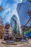 The famous Gherkin Tower with statues on street. London Stock Photography