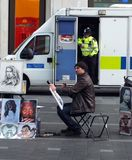 A street artist painting cartoons and portraits works in leicester square while a police man stands in the door of a van. London, England - November 03, 2017: a royalty free stock image