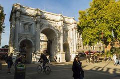 People on the street near Marble Arch, monument modeled after the Constantine Arch in Rome and Arc D` Triumph in Paris. London, ENGLAND - October 25 2017: People Stock Images