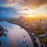 London, England - Panoramic aerial skyline view of east London at sunrise with skycrapers of Canary Wharf. And beutiful colorful sky at background royalty free stock photo