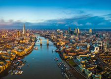 London, England - Panoramic aerial skyline view of London including Tower Bridge with red double-decker bus. Tower of London, skyscrapers of Bank District and stock image