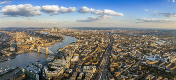 London, England - Panoramic aerial view of London. With the famous Tower and Tower Bridge and skyscrapesr of Canary Wharf at the background stock image