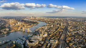 London, England - Panoramic aerial view of London with the famous Tower and Tower Bridge and skyscrapesr of Canary Wharf. At the background stock images