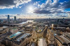 London, England - Panoramic skyline view of London taken from St. Paul`s Cathedral with iconic red double-decker buses. And beautiful sky and clouds Stock Image