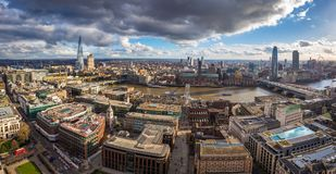 London, England - Panoramic skyline view of London with Millennium Bridge, famous skyscrapers and other landmarks. With beautiful sunshine and blue sky and royalty free stock image