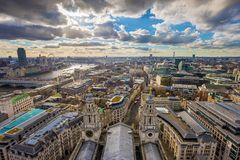 London, England - Panoramic skyline view of London taken from St. Paul`s Cathedral with red double-decker buses. London, England - Panoramic skyline view of Royalty Free Stock Photos