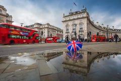 London England - 03 15 2018: Reflexion av röd dubbeldäckarebuLondon, England - 03 15 2018: Reflexion av röd dubbeldäckarebuse Royaltyfri Foto