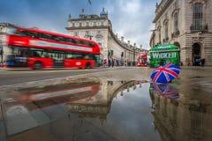 London England - 03 15 2018: Reflexion av röda dubbeldäckarebussar på flyttningen på den Piccadilly cirkusen Royaltyfria Foton