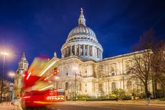 London, England - The Saint Paul`s Cathedral with famous old red double decker buses on the move. At night Stock Images