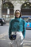 Beautiful and stylish A girl in a green furry sweater made of faux fur posing during the London Fashion Week. outside Eudon Choi Stock Image