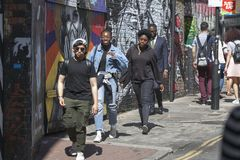 Young people walk along the sidewalk along Brick Lane Street. LONDON, ENGLAND - September 15, 2017 Young people walk along the sidewalk along Brick Lane Street Royalty Free Stock Photography