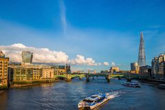London, England - Sightseeing boats at sunset on River Thames with Southwark Bridge and Tower Bridge Stock Photography