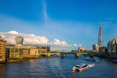 London, England - Sightseeing boats at sunset on River Thames with Southwark Bridge and Tower Bridge Stock Photo