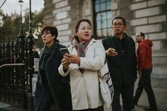 Asian people visiting London city. LONDON, ENGLAND - 25th October, 2018: Two women and a man from Asia, in casual attitude, searching directions while visiting royalty free stock images