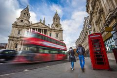 London, England - Tourist couple walking by a traditional red telephone box with red double-decker bus. And black taxi on the move at background at St.Paul`s royalty free stock photo