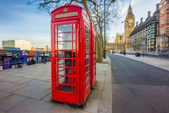 London, England - Traditional British red telephone box at Victoria Embankment with Big Ben. At background Royalty Free Stock Photo