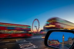 London, England - Traditional red double decker buses on the move on Westminster Bridge with Big Ben and Houses of Parliament Royalty Free Stock Images