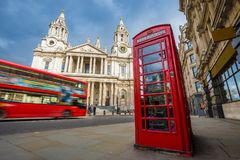 London, England - Traditional red telephone box with iconic red double-decker bus on the move at St.Paul`s Cathedral. On a sunny day Royalty Free Stock Photo