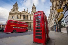 London, England - Traditional red telephone box with iconic red vintage double-decker bus on the move. At St.Paul`s Cathedral on a sunny day royalty free stock photography
