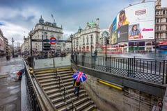 London, England - 15 03 2018: Turist, das britischen Regenschirm hält und unten unterirdisch zu Piccadilly geht Lizenzfreies Stockfoto