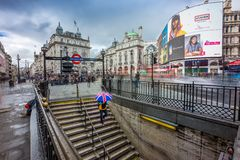 London, England - 15.03.2018: Turist holding british style umbrella. And going down to Piccadilly underground station Stock Photo