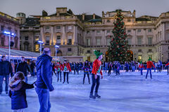 London, England, UK - December 29,2016:  People enjoying skating. At Somerset House at dusk and shows a large Christmas tree against the backdrop of the Stock Photos