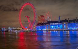 Enjoying a lovely view of the London eye lit with colorful lights at night from the westminster bridge stock images