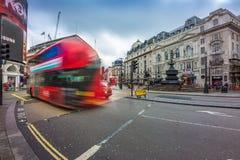 London England - 03 15 2018: Upptagen trafik på den Piccadilly cirkusen med iconic röda dubbeldäckarebussar på flyttningen Fotografering för Bildbyråer
