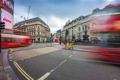London England - 03 15 2018: Upptagen trafik på den Piccadilly cirkusen med iconic röda dubbeldäckarebussar på flyttningen Arkivfoton