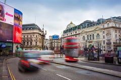 London England - 03 15 2018: Upptagen trafik på den Piccadilly cirkusen med den iconic röda dubbeldäckarebussen och svarttaxien Royaltyfri Bild
