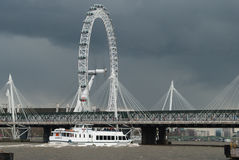 London Eye against grey sky. London Eye and Golden Jubilee Bridge against a dark April sky Royalty Free Stock Photography