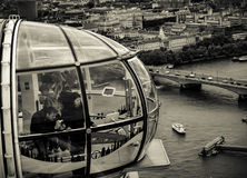 The London Eye Capsule - tourists. A picture of people/tourists in an London Eye capsule looking at the view across the famous Thames River in the capital of royalty free stock photo
