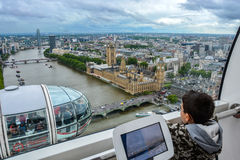 The London Eye Capsule - Young Boy looking out window at Skyline stock photos