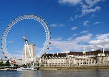London Eye & County Hall. View from a boat on the Thames of County Hall and the London Millenium Eye stock photography