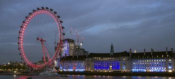 London Eye and County Hall by night, pink and blue. royalty free stock images