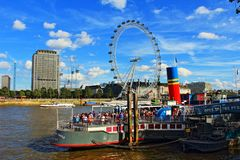 London Eye and moored boat pub Thames River Ehgland. London,United Kingdom-August 13th 2016:Scenic view of Thames River and South Bank with London Eye in nice stock photography