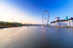 The London Eye near the River Thames  in London. LONDON, ENGLAND - May 14, 2016 : The London Eye near the River Thames  in London at dusk, England. The London Royalty Free Stock Photos