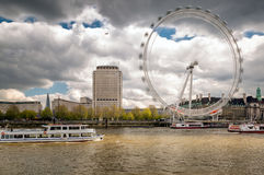 The London Eye spinning with river Thames in foreground Stock Photography