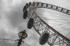 London Eye and streetlights from below in a cloudy English sky Royalty Free Stock Images