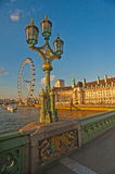 London Eye at sunset from Westminster Bridge. London Eye and South Bank of River Thames viewed at sunset in golden light from Westminster Bridge Stock Image