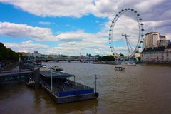 The London Eye on the Thames River on a slightly cloudy spring day stock photography