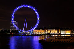 The London Eye, the touristic big wheel, by night. The London Eye, the big wheel tourist attraction, shines in the night sending its blue reflex on the river royalty free stock images