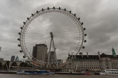 London Eye viewed across Thames river at dusk in late October. Under the gloomy sky royalty free stock image