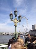 London Eye from Westminster Bridge. A view of London Eye from Westminster Bridge with old street lamp on a sunny day Royalty Free Stock Photo