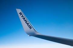 LONDON FÖRENADE KUNGARIKET - April 12, 2015: Ryanair logo på flygplans vingspets i mitt--luft över Förenade kungariket Royaltyfria Foton
