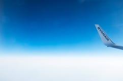 LONDON FÖRENADE KUNGARIKET - April 12, 2015: Ryanair logo på flygplans vingspets i mitt--luft över Förenade kungariket Arkivbild