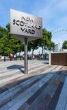 LONDON FÖRENADE KUNGARIKET - AUGUSTI 28, 2017 - nytt Scotland Yard tecken med det London ögat i bakgrunden Arkivbild